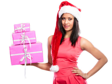 multiple ethnicities: Christmas winter happiness concept. Girl mixed race woman wearing red dress santa helper hat holding stack of pink presents gift boxes on white