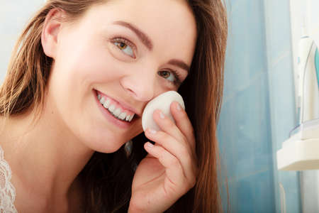 girl  care: Woman removing makeup with cotton swab pad. Young girl taking care of skin. Skincare concept. Stock Photo