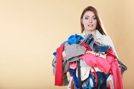 Woman with stack pile of dirty laundry clothes. Girl cleaning tidying.