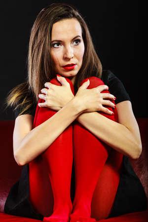 pantimedias: Mujer triste color vivo pantimedias sentada en el sof� de fondo negro