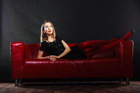 pantimedias: Equipo de la manera elegante. Piernas largas mujer de moda en rojo vivo pantimedias de colores relajantes en el sofá de interior en negro Foto de archivo