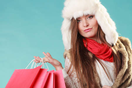 gorgeous woman: Charming gorgeous woman with bags shopping. Young girl in fur hat in studio blue. Winter fashion clothes sale.