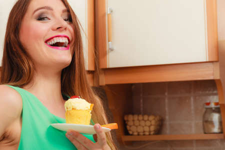 gluttony: Woman holding delicious cake with sweet cream and fruits on top. Appetite and gluttony concept. Stock Photo
