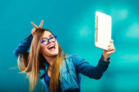 gente loca: La tecnología de Internet moderno concepto de estilo de vida. muchacha que usa la tableta digital teniendo una imagen de sí misma. selfie estilo. Mujer con lector de libros electrónicos touchpad de color azul pc