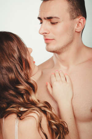 half naked: Seductive alluring passionate young couple lovers embracing in studio. Handsome muscled half naked semi nude man and woman in lingerie. Love and passion. Stock Photo