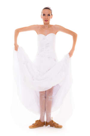 indecision: Wedding day. Running bride funny young woman wearing sport shoes isolated on white background Stock Photo