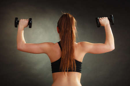 woman bra: Bodybuilding. Strong fit woman exercising with dumbbells. Muscular long hair girl lifting weights on black