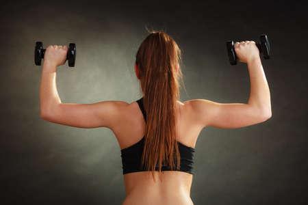 levantar pesas: Culturismo. Mujer fuerte ajuste que ejercita con pesas. Musculares largas pesos de elevación de la muchacha del pelo en negro Foto de archivo
