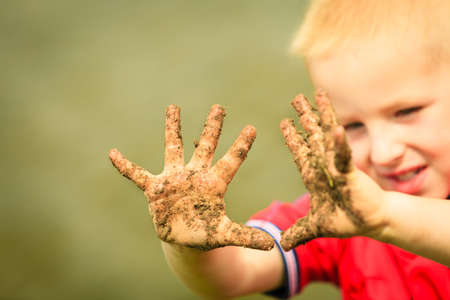 hapy: Child little blonde boy kid playing outdoor showing dirty muddy hands. Hapy childhood.