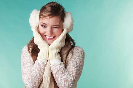 blinking: Portrait of smiling cute pretty woman in earmuffs blinking winking. Happy lovely girl in studio on green.