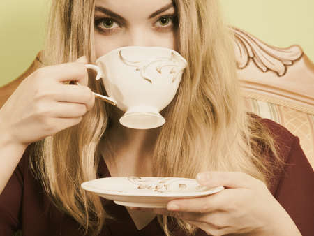 old fashioned sepia: Fashionable woman drinking cup of coffee sitting on vintage sofa. Young girl with hot energizing beverage stay awake. Caffeine energy. Sepia.