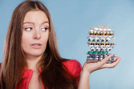 drug abuse: Woman holding pills. Girl female with stack of tablets. Drug addict and health care concept. Overdose. Stock Photo