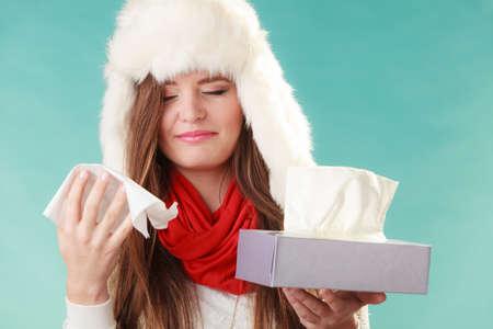 gripa: Mujer enferma en sombrero de piel estornudos en el tejido. Muchacha enferma atrapado invierno frío gripe en estudio en verde.