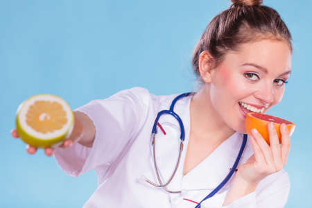eating right: Happy dietitian nutritionist holding grapefruit having fun. Woman promoting healthy food fruit. Right eating nutrition and slimming concept.