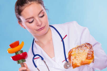 eating right: Dietitian nutritionist with sweet roll bun and vegetables like cucumber, tomato and pepper. Woman holding comparing junk and healthy food. Right eating nutrition concept.