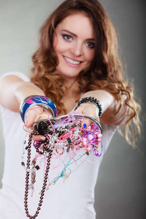 plentiful: Happy pretty young woman wearing bracelets and rings holding many plentiful of precious jewelry necklaces beads. Portrait of gorgeous fashion girl in studio on gray.