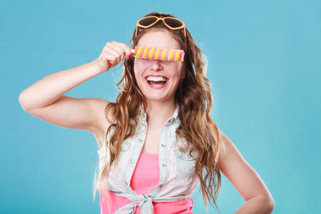 smilie: Summer holidays happiness concept. Happy joyful and cheerful young woman female model covering eyes with popsicle ice pop on blue background
