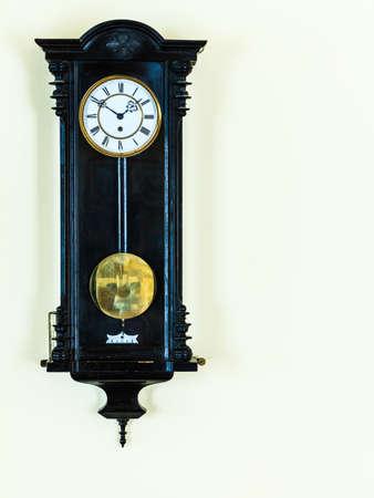 pendulum: old big wooden pendulum clock hanging on wall