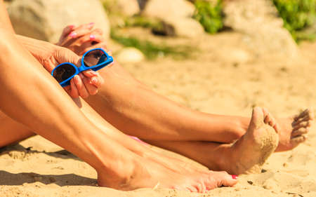 sun tanning: Closeup of women legs sun tanning and relaxing on beach. Friends with sunglasses resting at sea. Summer relax. Stock Photo