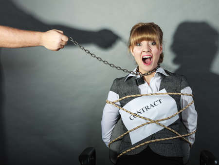 tied girl: Scared businesswoman bound by contract terms and conditions.  Afraid and helpless woman tied to chair become slave. Human hand hold chain and has power over girl. Business and law concept. Stock Photo