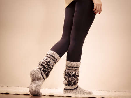 Winter fashion. Woman legs in black pantyhose and stylish fashionable woolen warm socks