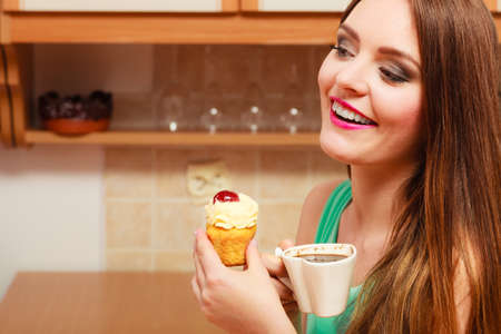 gluttony: Woman drinking coffee and eating delicious gourmet sweet cream cake. Glutton girl sitting in kitchen with hot beverage and cupcake. Appetite and gluttony concept.