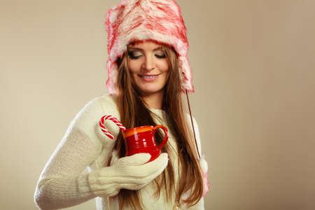 sweater girl: Young woman holding xmas mug with candy cane. Girls hands in woolen white gloves. Christmas time concept.