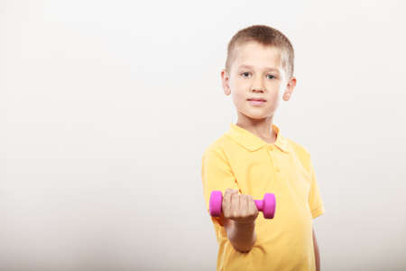 care about the health: Sports little boy making exercise with dumbbell. Care about health and body Stock Photo