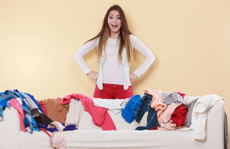 freaking: Desperate helpless freaking out woman standing behind sofa couch in messy living room. Young girl surrounded by many stack of clothes. Disorder and mess at home.