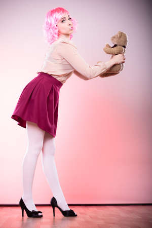 mental disorder: Mental disorder concept. Young childlike woman wearing like puppet doll holding teddy bear toy studio shot
