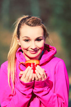 care about the health: Young pretty girl at park holding mug with hot tea and warming hands. Woman care about health sitting on fresh air.