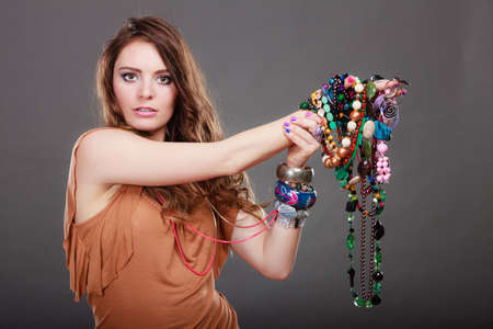 gorgeous girl: Pretty young woman wearing bracelets and rings holding many plentiful of precious jewelry necklaces beads. Portrait of gorgeous fashion girl in studio on gray.