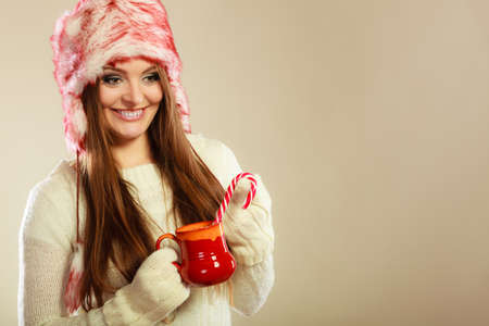 sweater girl: Young woman with xmas mug pulling candy cane. Girls hands in woolen white gloves. Christmas time concept. Stock Photo