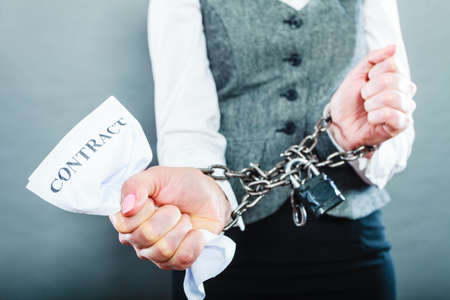 bound woman: Business concept. Serious woman businesswoman with chained hands holding contract, side view grungy background