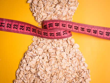 Concepto de dieta adelgazan abajo de comer sano. Mujer la forma vestido hecho de harina de avena con cinta métrica alrededor de la cintura delgada de color amarillo