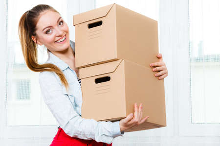 moving in: Happy woman moving in carrying cartons boxes. Young girl arranging interior and unpacking at new apartment house home. Stock Photo