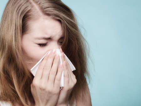 Grippe rhume ou une allergie symptôme. Sick woman girl éternuements dans le tissu sur fond bleu. Les soins de santé.