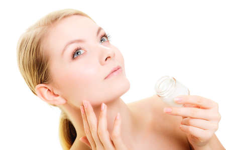 complexion: Skincare. Young woman taking care of her dry complexion. Girl applying moisturizing cream isolated. Beauty treatment.