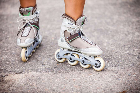 dynamic activity: Enjoying roller skating rollerblading on inline skates sport in park. Outdoor activities. Part of human legs in sport shoes.