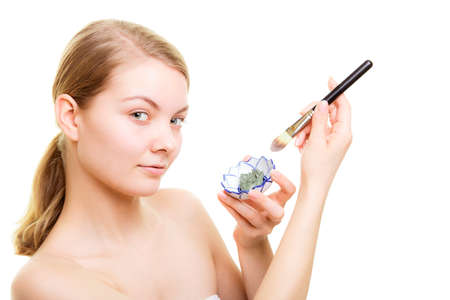 complexion: Skin care. Woman applying with brush clay mud mask on face isolated. Girl taking care of dry complexion. Beauty treatment.