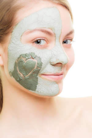 purifying: Skin care. Woman in clay mud mask with heart symbol of love on cheek isolated on white. Girl taking care of dry complexion. Beauty treatment. Stock Photo