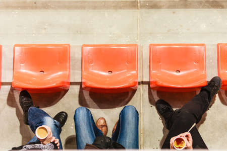 reserved seat: Sport competitions, recreation and relax. Row of plastic chairs and human legs in football stadium. Hot drink disposable cups with tea and coffee in hands. Stock Photo