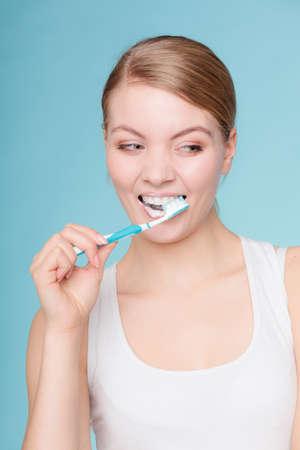higiene bucal: Mujer joven cepillarse los dientes de limpieza. Muchacha con el cepillo de dientes. Higiene oral. Foto de archivo