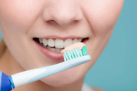 Pretty young girl with electric brush cleaning white teeth using toothpaste. Happy woman clean her oral cavity caring about dental health.