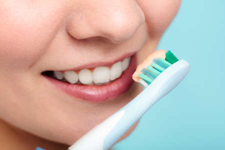 Young woman brushing cleaning teeth. Girl holds toothbrush with toothpaste on it. Oral hygiene. Stock Photo