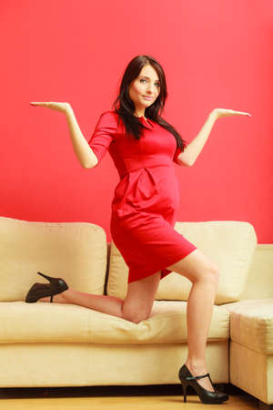 mothering: Stylish pretty girl in red dress. Pregnant woman at home with open hands palm. Prospective mothering concept.