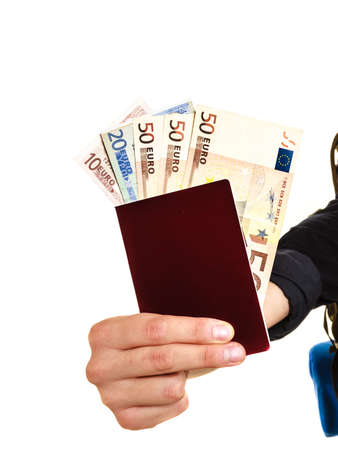 spendthrift: Human tourist hand holding passport full of money. Summer vacation travel. Isolated on white background. Stock Photo