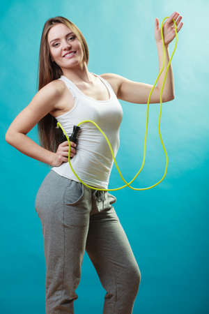 actively: Young fit slim woman spend actively free time. Beauty happy girl wearing sports clothes with jumping skipping rope on blue background. Stock Photo