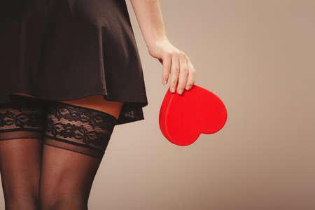 sexualidad: Belleza, la sexualidad y la seducci�n. Mujer parte del cuerpo atractivo con el rect�ngulo rojo del coraz�n de regalo presente en el estudio.