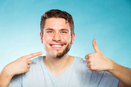 handsome guy: Portrait of happy man with half shaved face beard hair. Smiling handsome guy on blue showing thumb up gesture. Skin care and hygiene.